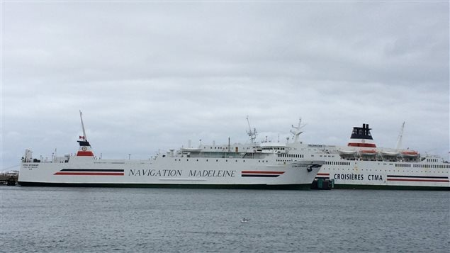 À l'avant-plan, le CTMA Voyageur, un navire cargo, au port de Cap-aux-Meules