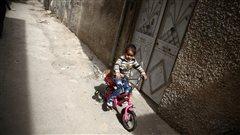 Une jeune Syrienne fait du vélo dans un quartier situé au nord-est de Damas.