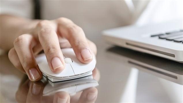 Une main utilise une souris d'ordinateur