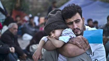 A Syrian refugee and his child wait at a resting point to board a bus on the Greek island of Lesbos in October. We see a dark-haired man with a slight, dark beard dressed in white. His enormous arms hug a child, who appears to be two or three, in his lap. The child wears a grey toque. He is sound asleep.
