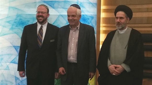 From left. Rabbi Cory Weiss, Immigration Minister John McCallum and Imam Seyed Reza Hoseini-Nasab at the the March 6 launch of the Temple Har Zion and Imam Mahdi Islamic Centre refugee program. Rabbi Weiss wears a buttoned up dark suit, striped tie, glasses and a yarmulke.  He has a dark beard and his hair appears to be thinning just a bit. He is smiling widely. Mr. McCallum wears a brown suit with no tie and a yarmulke. As he does often these days, he is smiling. The Imam wears a dark robe and turban. His collar is white and his hands are cupped in front of him at the waste. He wears a tight smile.