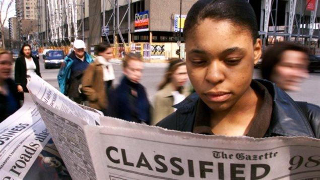 Une femme cherche du travail dans les pages du quotidien anglais The Gazette de Montréal. Photo crédit CBC