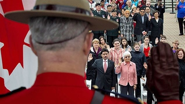 Des nouveaux arrivants deviennent des citoyens canadiens après avoir prêté serment lors d'une cérémonie officielle.
