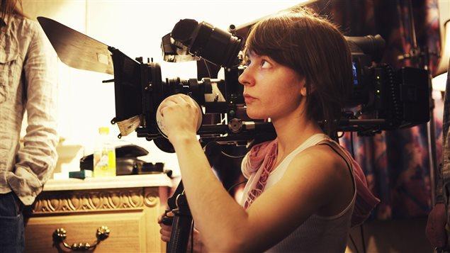 Une réalisatrice manipule une caméra.