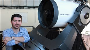 Jesse Rogerson, PhD candidate in astrophysics at York University stands by one of the university's smaller telescopes. He led the international research which made the discovery