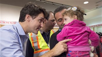 Canada's Prime Minister Justin Tudeau (left) went to Montreal's airport to welcome Syrian refugees soon after being elected in late 2015.