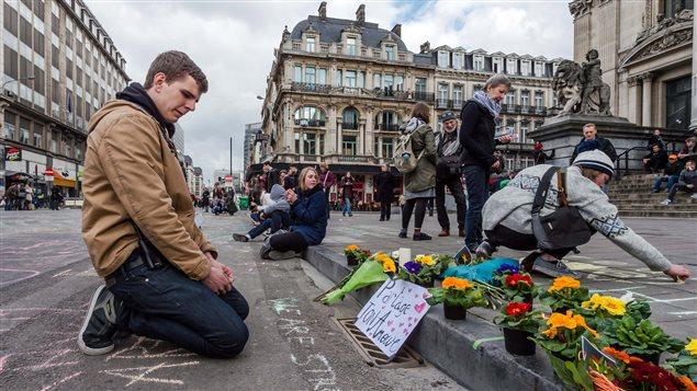 Un homme regarde des messages laissés à la mémoire des victimes des attaques de Bruxelles.