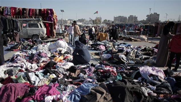 On Feb. 15, 2016 a Palestinian woman scours a used clothing market in Gaza. Demand for clothing is said to be an indicator of poverty and unemployment levels.