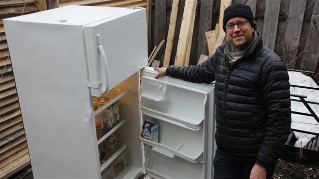 Patrick Bodnar pose � c�t� du frigo qu'il a install� dans sa ruelle � Rosemont.