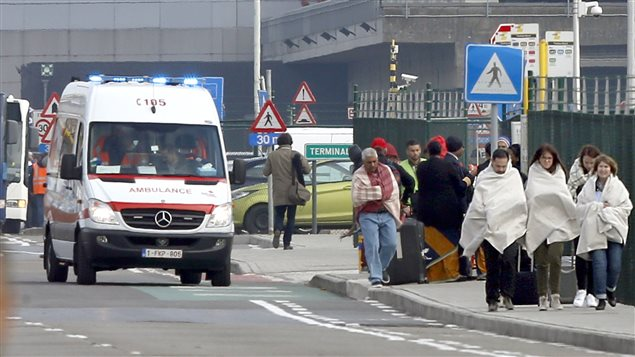 People wrapped in blankets leave the scene of explosions at Zaventem airport near Brussels, Belgium, March 22, 2016.