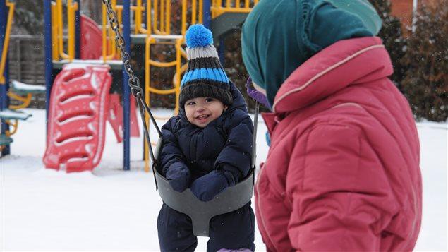 Le jeune Hussein, 10 mois, découvre les joies de l'hiver en compagnie de sa maman Roqaya