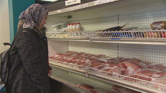 Une dame devant un étalage de viande halal