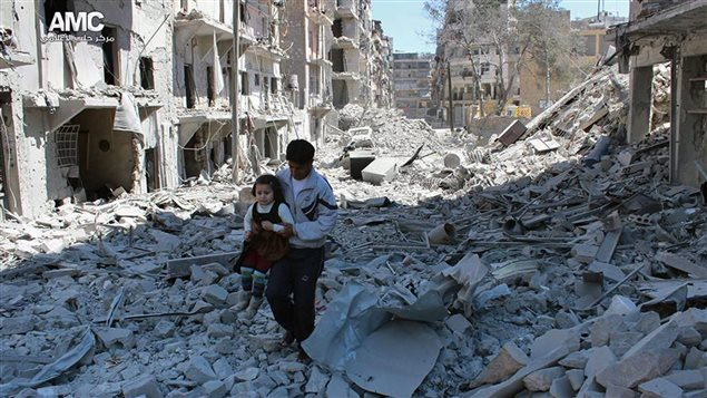 In This April 21, 2014, file photo shows a Syrian man holding a girl as he stands on the rubble of houses that were destroyed by Syrian government forces air strikes in Aleppo, Syria.