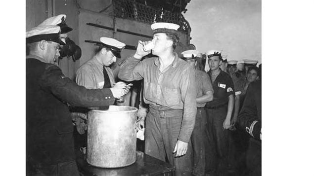 Ordinary Seaman Ernest Weir receives an extra rum ration during Victory over Japan celebrations aboard HMCS Prince Robert, Sydney, Australia, 16 Aug 1945