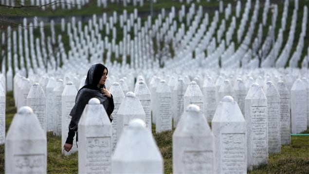In this photo taken on Sunday, March 20, 2016, a Bosnian woman walks among gravestones at Memorial Centre Potocari near Srebrenica, Bosnia and Herzegovina.