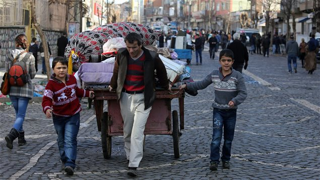 In this photo taken on Wednesday, Feb. 3, 2016, a family leave the Sur district in Diyarbakir, Turkey. The family are among tens of thousands displaced by fighting raging between Turkish security forces and militants in the southeast after a peace process collapsed in the summer.