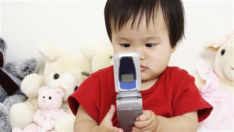 Un enfant tient un vieux cellulaire dans ses mains