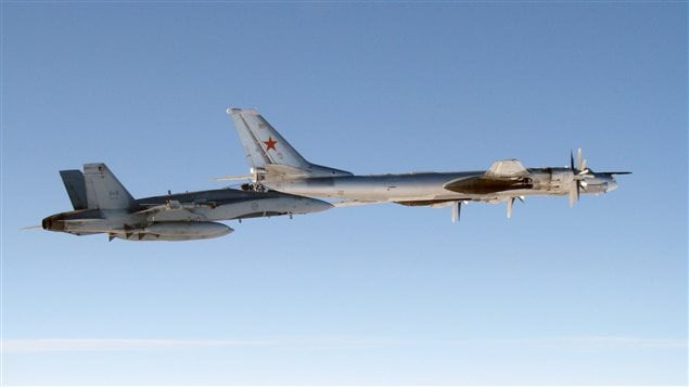 A CF-18 Hornet (left) from 4 Wing Cold Lake flies next to a Russian Tu-95 Bear bomber on Sept. 5, 2007.