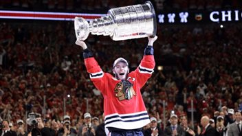 Chicago defeated the Tampa Bay to win the 2015 Stanley Cup. At least the man hoisting the Cup is Canadian--Jonathan Toews of Winnipeg. We see Toews from the knees up. He wears the red hawks jersey with its famous logo and the letter C on his left shoulder. Toews has a look of ecstasy as he hoists the cup over his head.