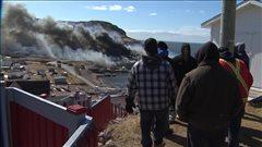 Des résidents observent les ruines fumantes de l'usine de poisson de Bay de Verde.