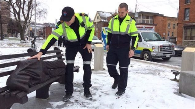 Paramedics approach a figure on a bench in a photo from the Hamilton Paramedics Twitter page. The statue in Hamilton is getting a lot of attention from paramedics as a recent blast of wintry weather has resulted in calls about a homeless person sleeping on a bench. The realistic looking blanket covered figure and bench are in fact made of bronze. The sculpture by an Ontario artist is called *homeless Jesus*