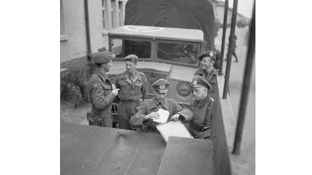 British and German officers standing between Canadian designed and built CMP 60cwt trucks, sign the truce deal on 12 April 1945