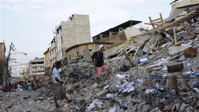 Des résidents de Portoviejo en Équateur marchent à travers les débris d'un hotel qui s'est effondré après le tremblement de terre.