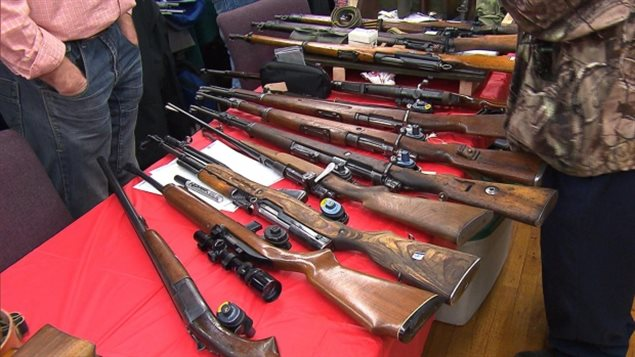 Long guns displayed at a gun show in Quebec in January 2016. The Quebec government wants to create a registry for such guns saying it will cost about $17-20 million, and then about $5 million a year to maintain.