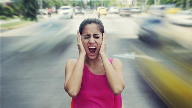 Une femme se bouche les oreilles à cause du bruit de la circulation