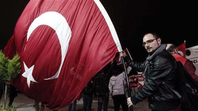 Un manifestant en faveur du laïcisme arbore un drapeau turc, en attendant la libération du général à la retraite Ilker Basbug en mars 2014, près d'Istanbul.