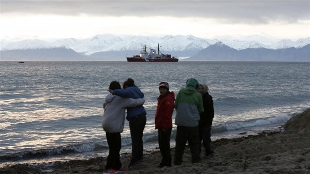 Local children stand on the shore as the Coast Guard ship Des Groseilliers sits in the waters near the Arctic community of Pond Inlet, Nunavut August 23, 2014. Chris Wattie/REUTERS