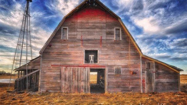 La chaise photographiée dans une des ouvertures d'une grange.