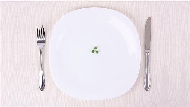 Une assiette avec trois petits pois verts