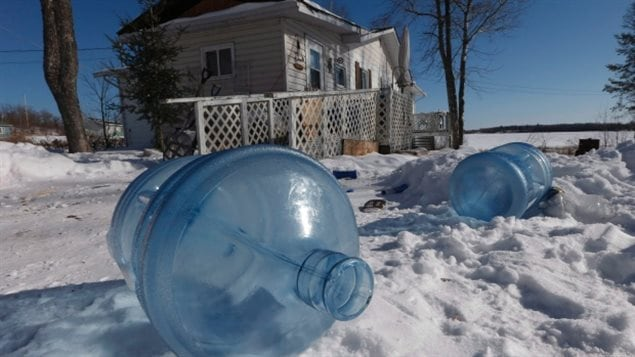 Empty 20 litre water bottles sit outside a house on Shoal Lake 40, waiting for pick up. Despite supplying water to the city of Winnipeg, the community has been under a boil water advisory for 19 years. We see two large light blue water bottles lying in the snow under blue skies on a pristine winter's day. In the background sit a ramshackle greyish house with a trelis-like fence that appears to be collapsing.