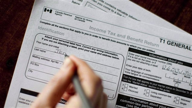 "Increased measures are helping the government collect more money from potential tax cheats. We see a closeup of the top page T-1 general tax form with the corners of two other parts of the form underneath it. And we see a hand holding a pen signing the top square. So far, all that's written in ""Jen."""