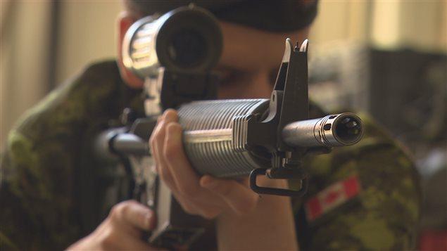 Un soldat des Forces armées canadiennes fait la démonstration de l'utilisation d'une arme à feu.