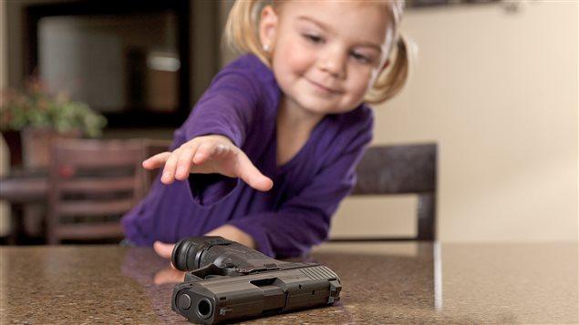 Une petite fille tente de prendre un pistolet