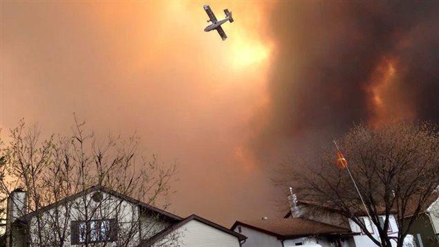 Un avion survole un quartier en feu de Fort McMurray.