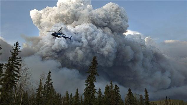 Un hélicoptère survole le feu de forêt dans la région de Fort McMurray.