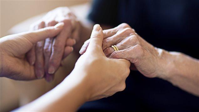 Une personne âgée et une personne plus jeune se tiennent par la main.