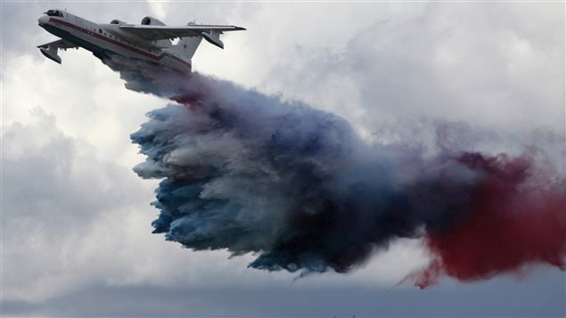 A Russian-made Beriev Be-200ChS amphibious aircraft, owned by the Siberian Regional Centre of the Russian Emergencies Ministry, dumps some 12 tons of coloured water matching the Russian state flag during a demonstration flight at an air show dedicated to the Day of the Russian Air Fleet at the Yemelyanovo airport outside Krasnoyarsk August 18, 2012.