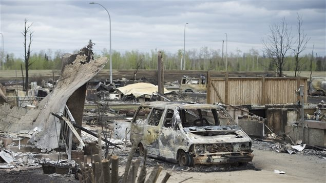 A van burned by a wildfire stands in the Beacon Hill neighborhood during a media tour of the fire-damaged city of Fort McMurray, Alberta, on Monday, May 9, 2016. The Beacon Hill neighborhood was a scene of utter devastation with homes burned down to their foundation.