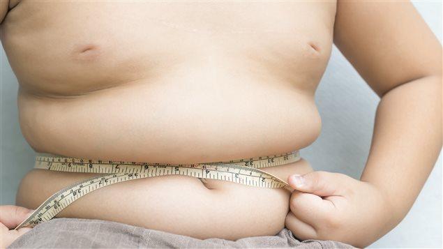 Un enfant mesure son ventre avec un ruban