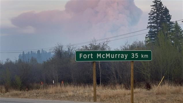 Une pancarte annonçant la ville de Fort McMurray en Alberta. En arrière-plan, la fumée des feux qui ont ravagé la ville durant la première semaine de mai.