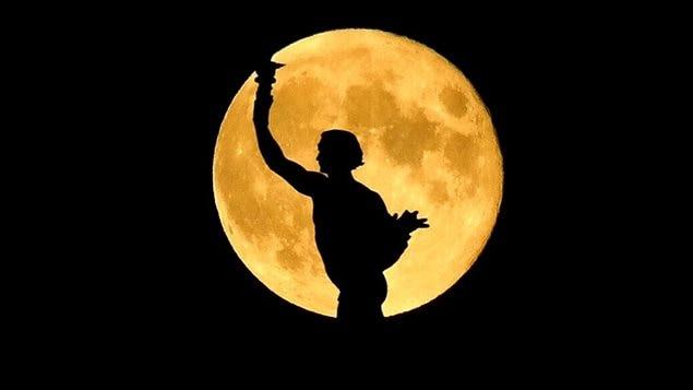 La statue du Golden Boy, qui trône au sommet du dome du palais législatif du Manitoba, à Winnipeg, est photographiée avec une pleine lune en arrière-plan, le 8 octobre 2014.