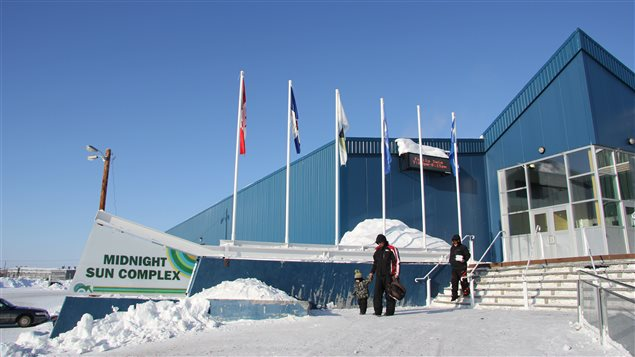 A photo of Inuvik's Midnight Sun Complex, home to the town's aquatic centre, in Canada's Northwest Territories on a sunny day with a family coming out of the front door.