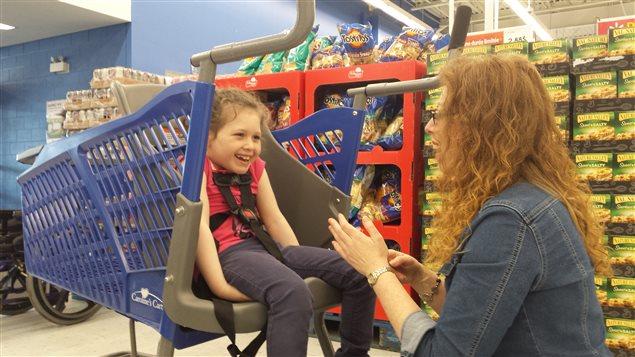 Grâce au «chariot de Caroline», Stéphanie Leclerc peut magasiner plus facilement avec sa fille Sarah, qui souffre d'un important retard de développement.