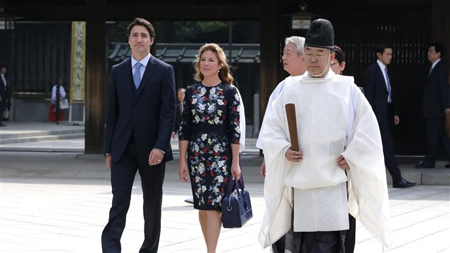 Canadian Prime Minister Justin Trudeau, left, and wife Sophie Gregoire Trudeau, second left, visit the Meiji Shrine, escorted by a shinto priest in Tokyo, Japan, on Tuesday, May 24, 2016.