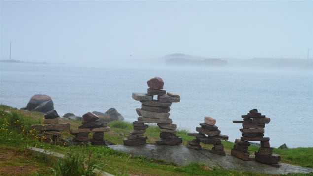 A group of five small inukshuks are shown on a hill overlooking the ocean in Labrador Canada.