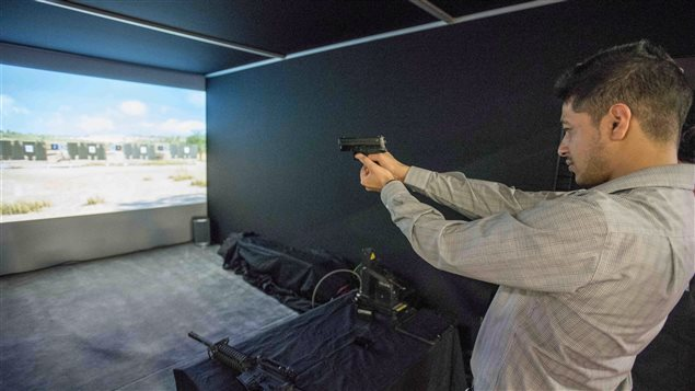 A delegate tries his hand at a realistic weapons simulator during the Canadian Association of Defence and Security Industries' CANSEC trade show in Ottawa on Wednesday, May 27, 2015.
